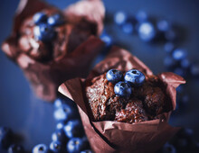 On A Blue Tray Are Two Chocolate Cupcakes In A Wrapper, And On Top Of Them And Around Them Are Blue Ripe Blueberries. Pastry With Berry Filling.