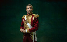 Wondered. Young Man In Suit As Nicholas II Isolated On Dark Green Background. Retro Style, Comparison Of Eras Concept. Beautiful Male Model Like Historical Character, Monarch, Old-fashioned.
