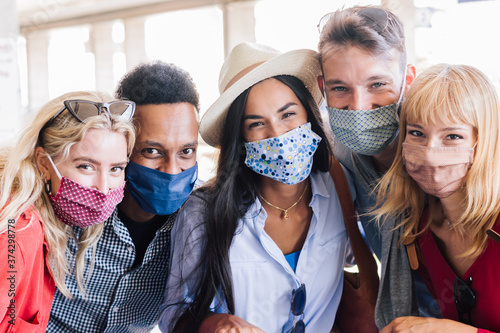 Portrait group of young happy friends wearing face mask during Covid pandemic smiling at the camera Canvas Print