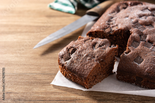 Photo Sweet chocolate sponge cake on wooden table.