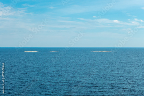 Vászonkép Three little white islands on blue background of water and cloudy sky on Ladoga