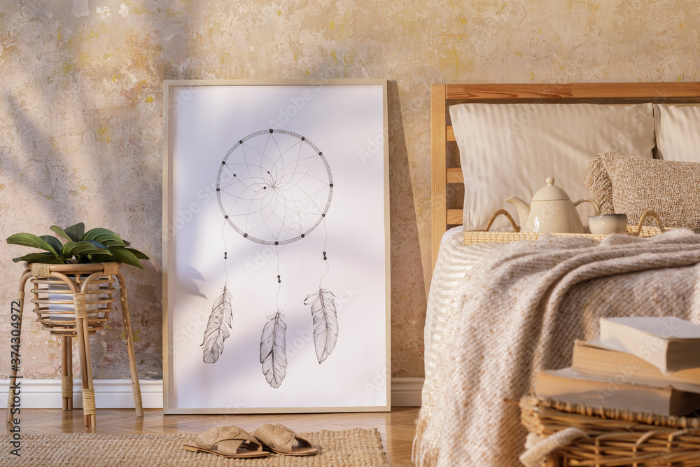 Fototapeta Stylish bedroom interior with mock up poster frame, design furniture, plant, rattan decoration and elegant personal accessories. Beautiful beige bed sheets, blanket and pillows. Template.