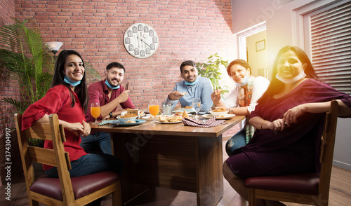 Indian asian young friends eating food in restaurant after corona virus pandemic Canvas