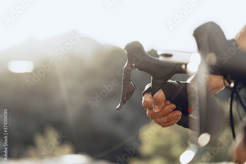 Hands of a professional cyclist in gloves on handle bar of a bicycle Fotobehang