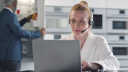 Mature business lady in bathrobe using headset and laptop for video chat sitting in kitchen