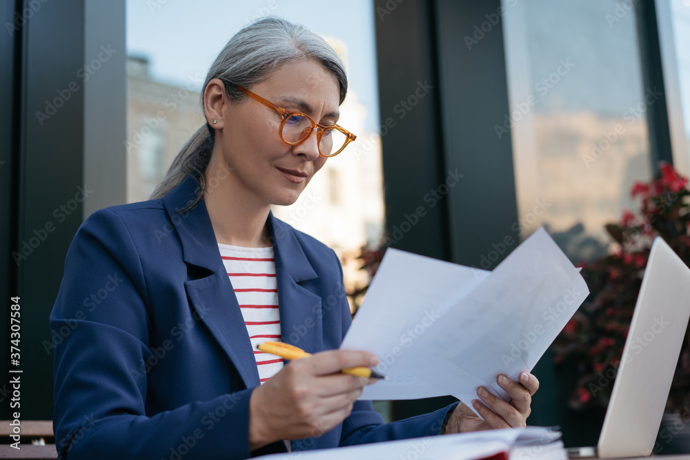 Fototapeta Pensive mature businesswoman reading contract, planning project, brainstorming. Portrait of middle aged asian secretary reading, working with documents, sitting at workplace