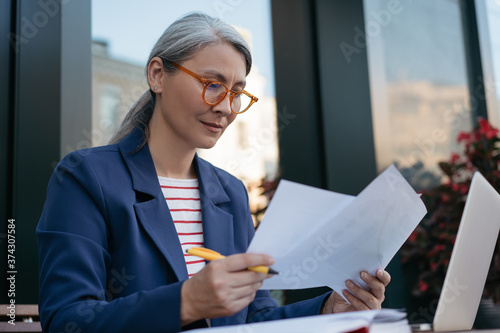 Fotografia Pensive mature businesswoman reading contract, planning project, brainstorming