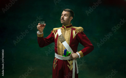 Royal whiskey. Young man in suit as Nicholas II isolated on dark green background. Retro style, comparison of eras concept. Beautiful male model like historical character, monarch, old-fashioned.