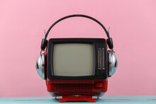 Red Retro Old Portable Mini Tv Set With Headphones On Pink Background.