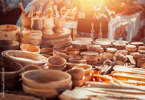 Obraz Group of wooden mortar and pestles, bowls, plates, spatulas on the countertop at antique bazaar. Shopping at sunday flea market. - fototapety do salonu