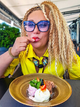 Pretty Woman With Curly Hair In Blue Glasses Eats Strawberries From Ice Cream In Riga, Latvia