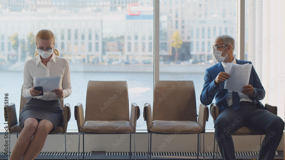 Fototapeta Two mature of businesspeople in mask sitting on chairs keeping social distancing in corridor