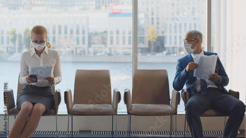 Obraz Two mature of businesspeople in mask sitting on chairs keeping social distancing in corridor - fototapety do salonu