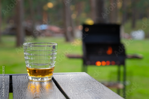 Fototapeta Whiskey glass on the wooden table next to burning grill outdoors in the back yard