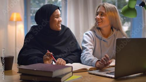 Arab and caucasian girls students preparing for seminar together sitting at desk Fototapet