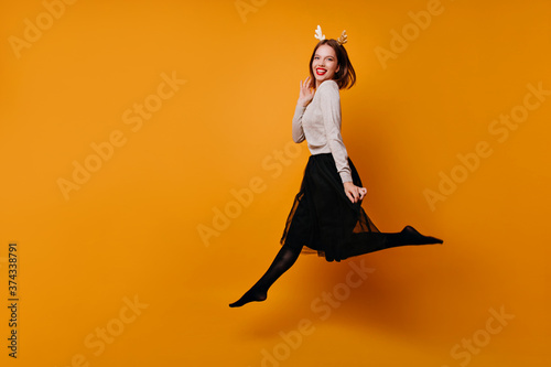 A joyful young girl in a lush black skirt, gray sweater and New Year's headband with golden reindeer horns jumps on an isolated orange background and looks into the camera Poster Mural XXL