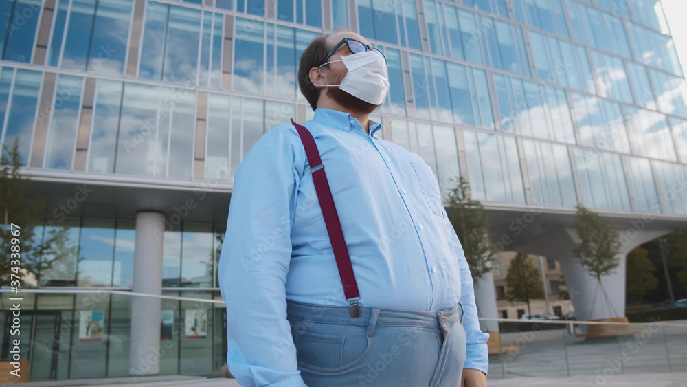 Fototapeta Overweight office employee tired of wearing safety mask outdoors