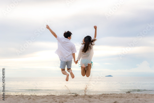 Fotografie, Obraz Happy Asian couple tourists jumping on beach vacations