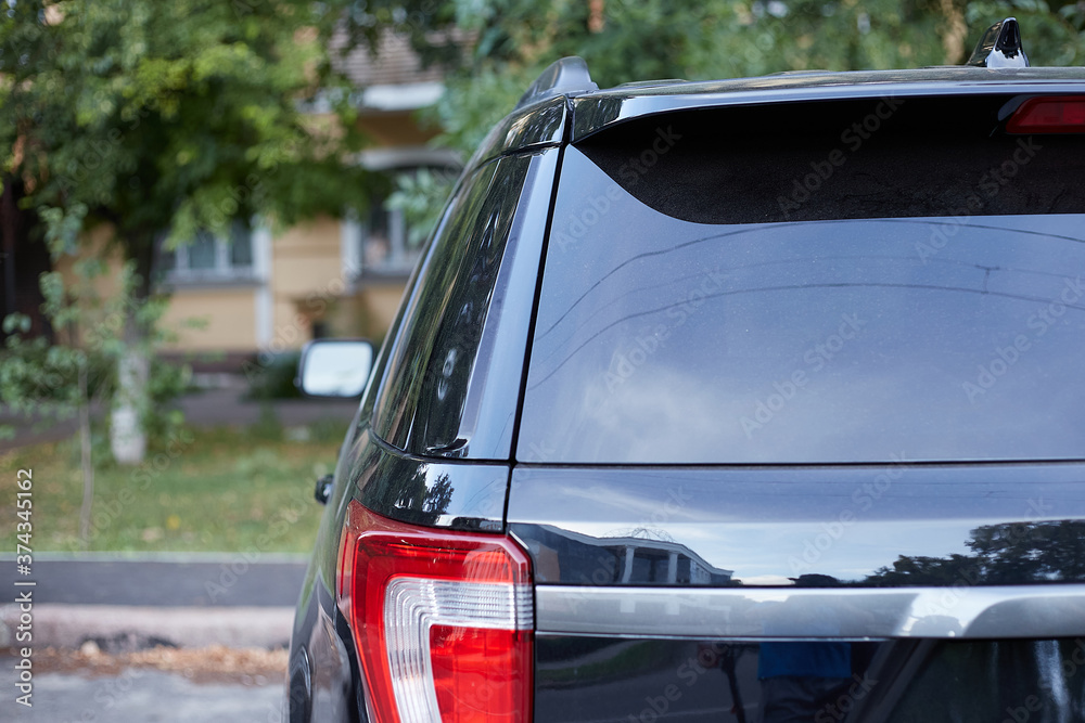 Fototapeta Back window of black car parked on the street in summer sunny day, rear view. Mock-up for sticker or decals