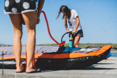 Fotografia Surfer women inflating kayak on the beach