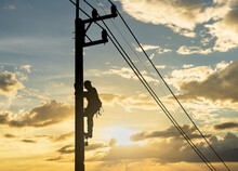 Silhouette Man Works With Electricity On A Pole With The Sunset In The Sky.