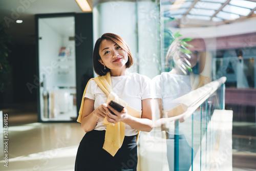 Half length portrait of pretty Japanese female influencer holding modern gadget Fototapeta