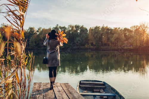 Woman walking on lake pier by boat admiring autumn landscape holding leaves Wallpaper Mural