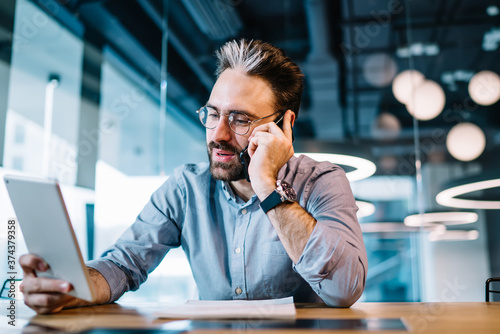 Man with tablet discussing business issue by phone