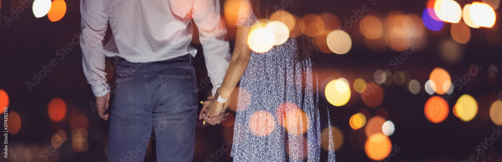 Fototapeta Romantic couple in love holds hands against backdrop of night city lights