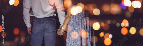 Fotografering Romantic couple in love holds hands against backdrop of night city lights