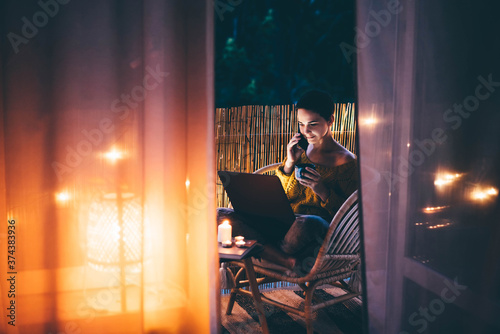 Canvas Print Woman using laptop at balcony of her apartment at the night.