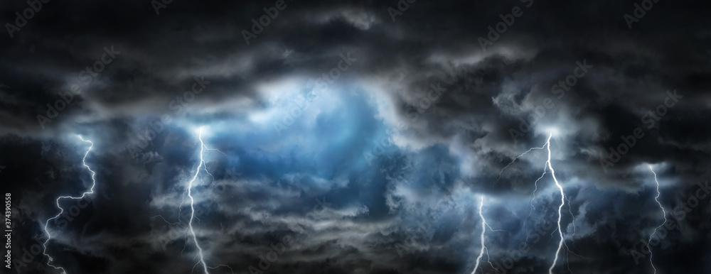 Fototapeta Sun rays, clouds and sparkling lightning in the dark sky. Thunderous dark sky with black clouds. Concept on the theme of weather, natural disasters, storm,  thunderstorms,, lightning.
