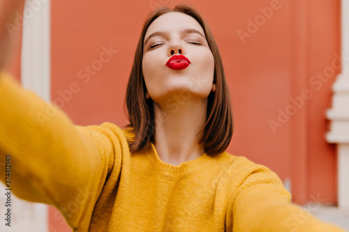 Amazing female model with bright makeup posing with kissing face expression and eyes closed Canvas