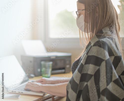 Foto Mujer utiliza mascarilla higiénica y gafas mientras teletrabaja desde casa duran