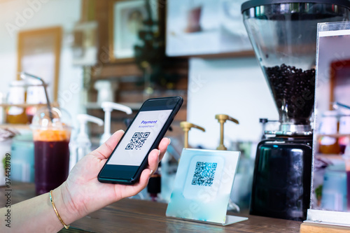Customer hand using smart phone to scan Qr code payment tag  with blurry coffee grinder in coffee shop to accepted generate digital pay without money Canvas Print