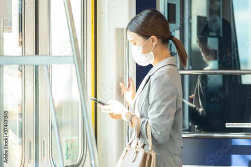 Fotomural マスク姿で電車通勤をする女性