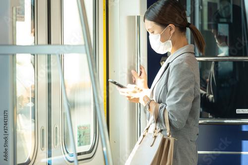マスク姿で電車通勤をする女性