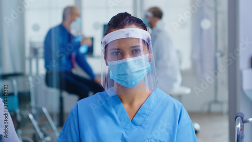 Obraz Medical assistant with visor and face mask against coronavirus looking at camera in hospital waiting area. Doctor consulting senior man in examination room. - fototapety do salonu
