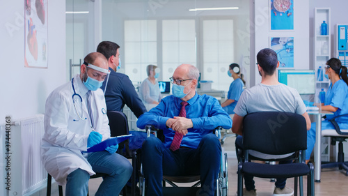 Doctor wearing face mask and visor against infection with coronavirus while talking with disabled senior man in waiting area sitting on wheelchair Billede på lærred