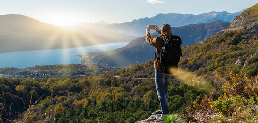 Traveler with a backpack and a smartphone stands on a mountain