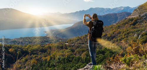 Fotografia Traveler with a backpack and a smartphone stands on a mountain