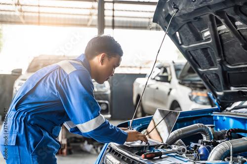 Fotografiet Mechanic Asian man using laptop computer examining tuning fixing repairing car e