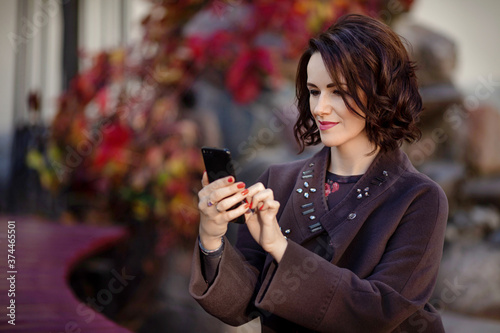 Attractive middle ade woman using smartphone while sitting on a bench in the city park Canvas Print