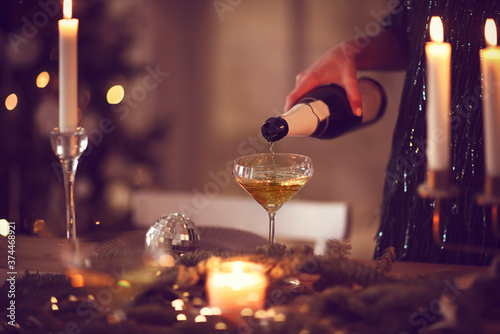 Photo Crop woman pouring champagne during Christmas celebration
