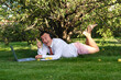 canvas print picture - Male manager working in the garden, lying on the lawn, holding an online meeting. He laughs and rejoices. He is wearing a shirt with a tie, underpants. Stay home and quarantine.