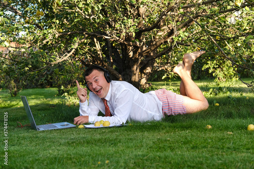 Male manager working in the garden, lying on the lawn, holding an online meeting Canvas Print
