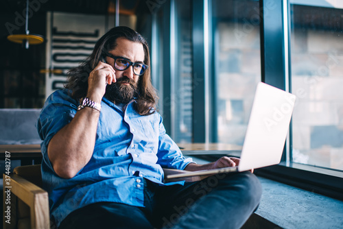 Fotografie, Obraz Serious caucasian mature male in eyewear for vision correction making call to op