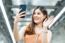 Young Asian Woman Passenger Using Smart Mobile Phone For Selfie Or Video Conference To Her Friend In Subway Interchange When Traveling In City,enjoy Weekend Vacation After Covid19 Relaxation Measures