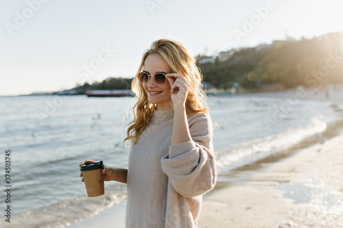 Photo Blissful blonde girl in cozy sweater posing at beach