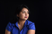 Portrait Of A Latin Woman Looking To The Side On Black Background